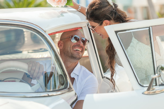 Husband laughing and smiling at bride sitting in an old Chevy car. Cuba destination wedding.
