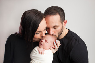 family kissing newborn baby.jpg