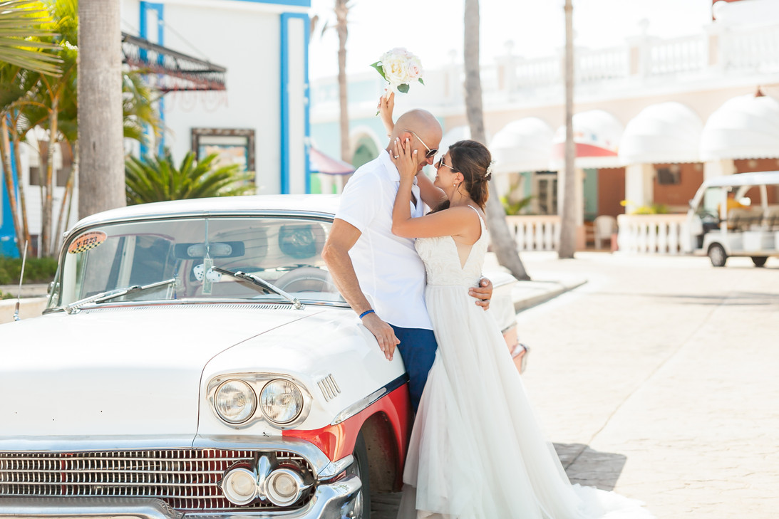 Bride and Groom leaning against old Chevy car about to kiss in Cuba. Destination Wedding. Bride holding wedding bouquet.