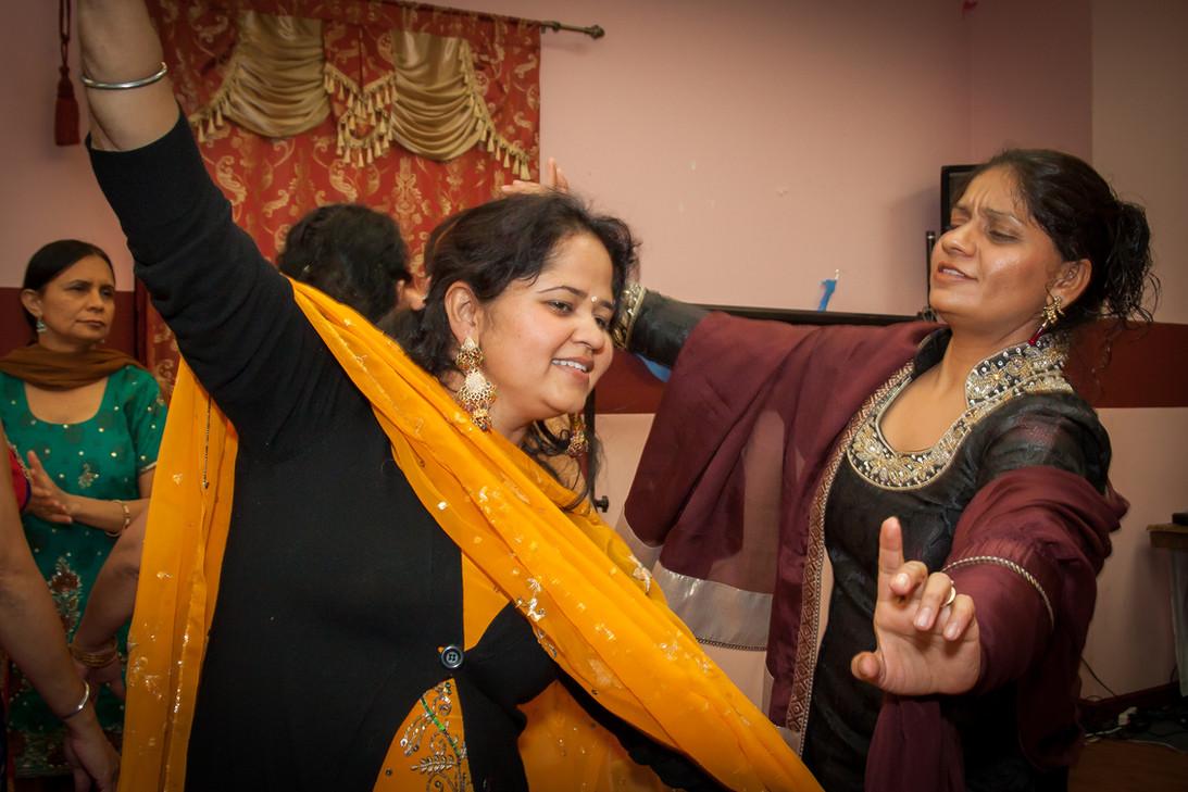 Two women dancing at a punjabi wedding party.