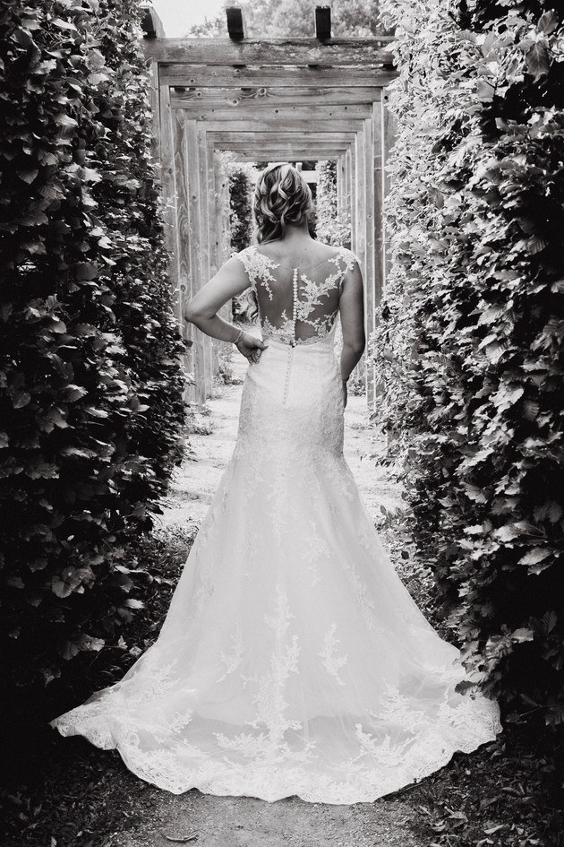 Bride standing in a vineyard wearing a wedding dress. Black and white wedding photo.