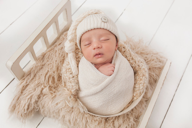 newborn baby boy with white hate wrapped in beige wrap.jpg