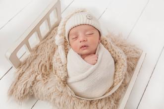 newborn baby boy with white hate wrapped in beige wrap.jpg