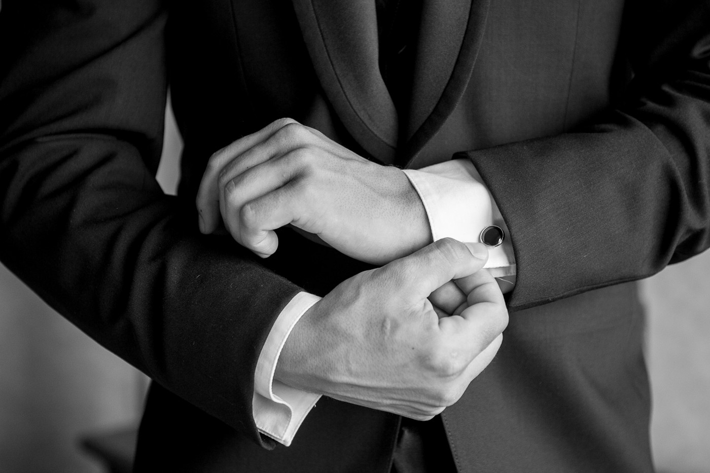 Close up of a groom getting ready. Suit cuffs.