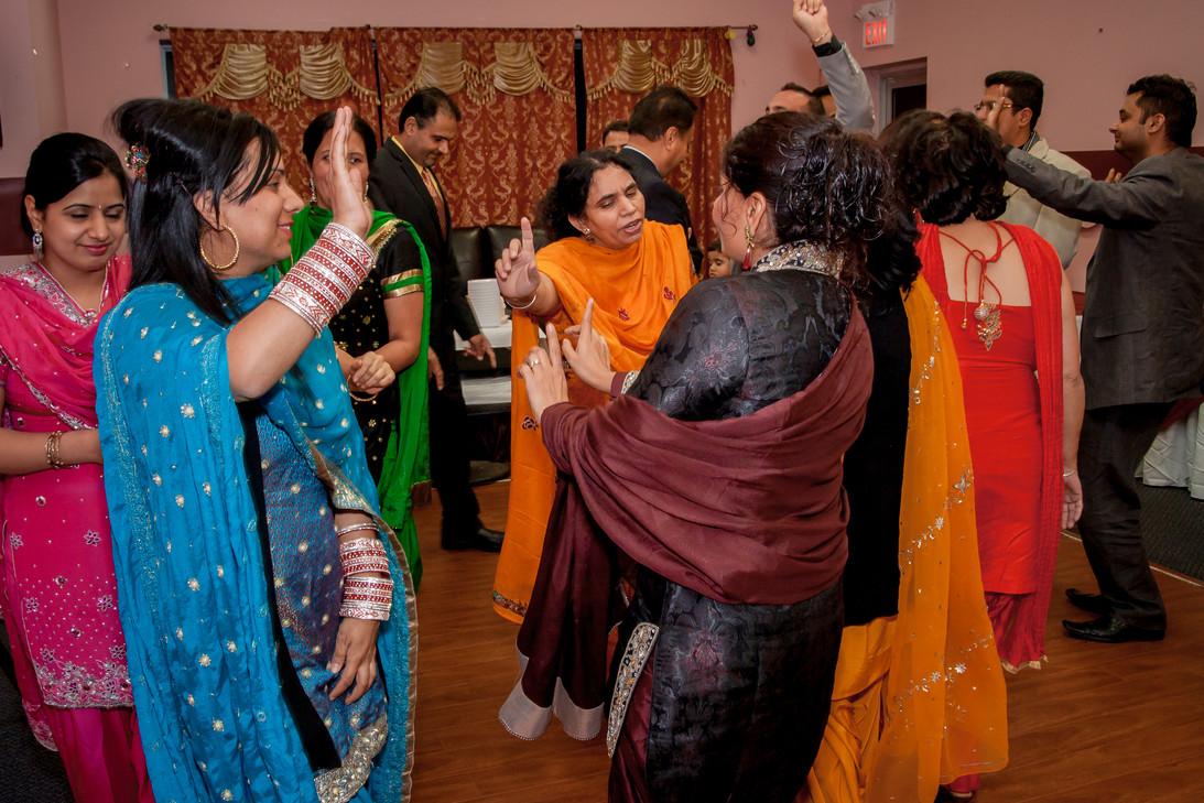 Women dancing at a punjabi wedding party. Various colourful dresses.