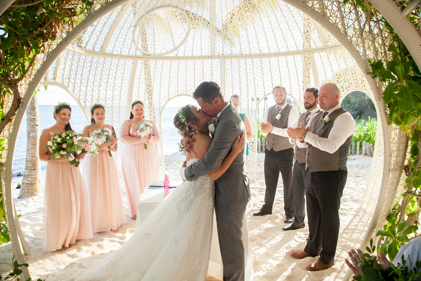 Husband and wife kiss for the first time as a married couple on a Mexico beach. Destination wedding. Wedding party standing around them.