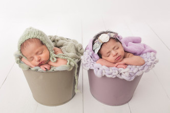Twin newborn bucket pose with green and purple wraps and buckets