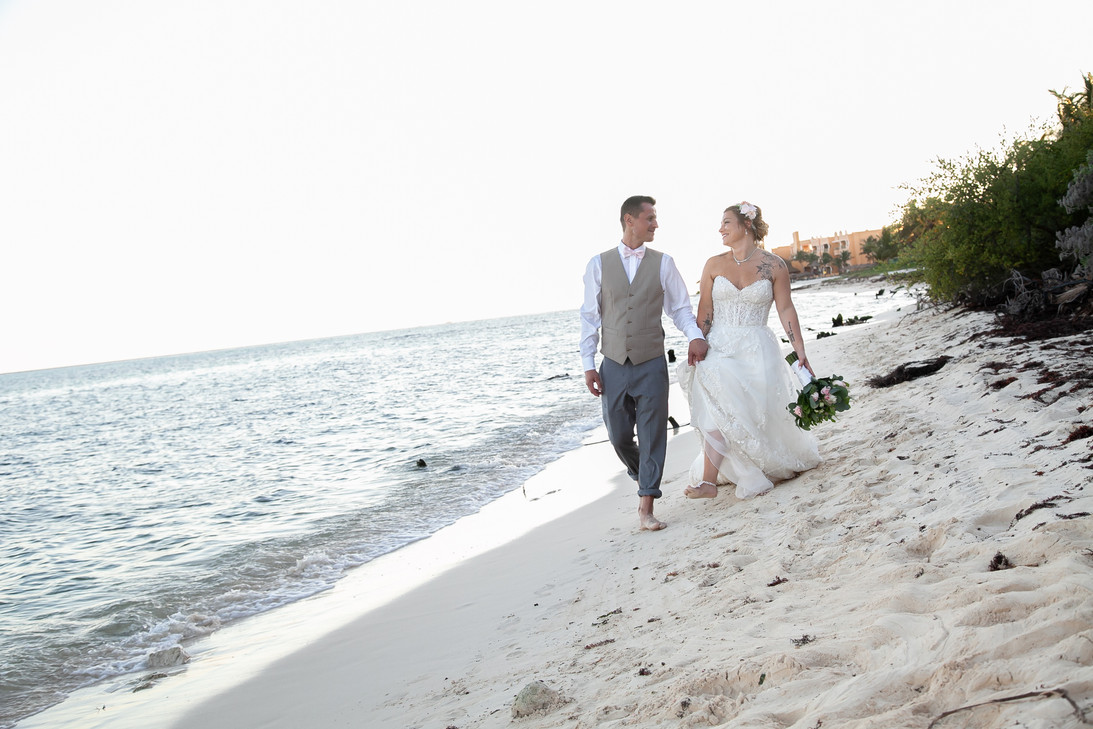 New married couple holding hands walking on the beach of Mexico. Destination wedding.