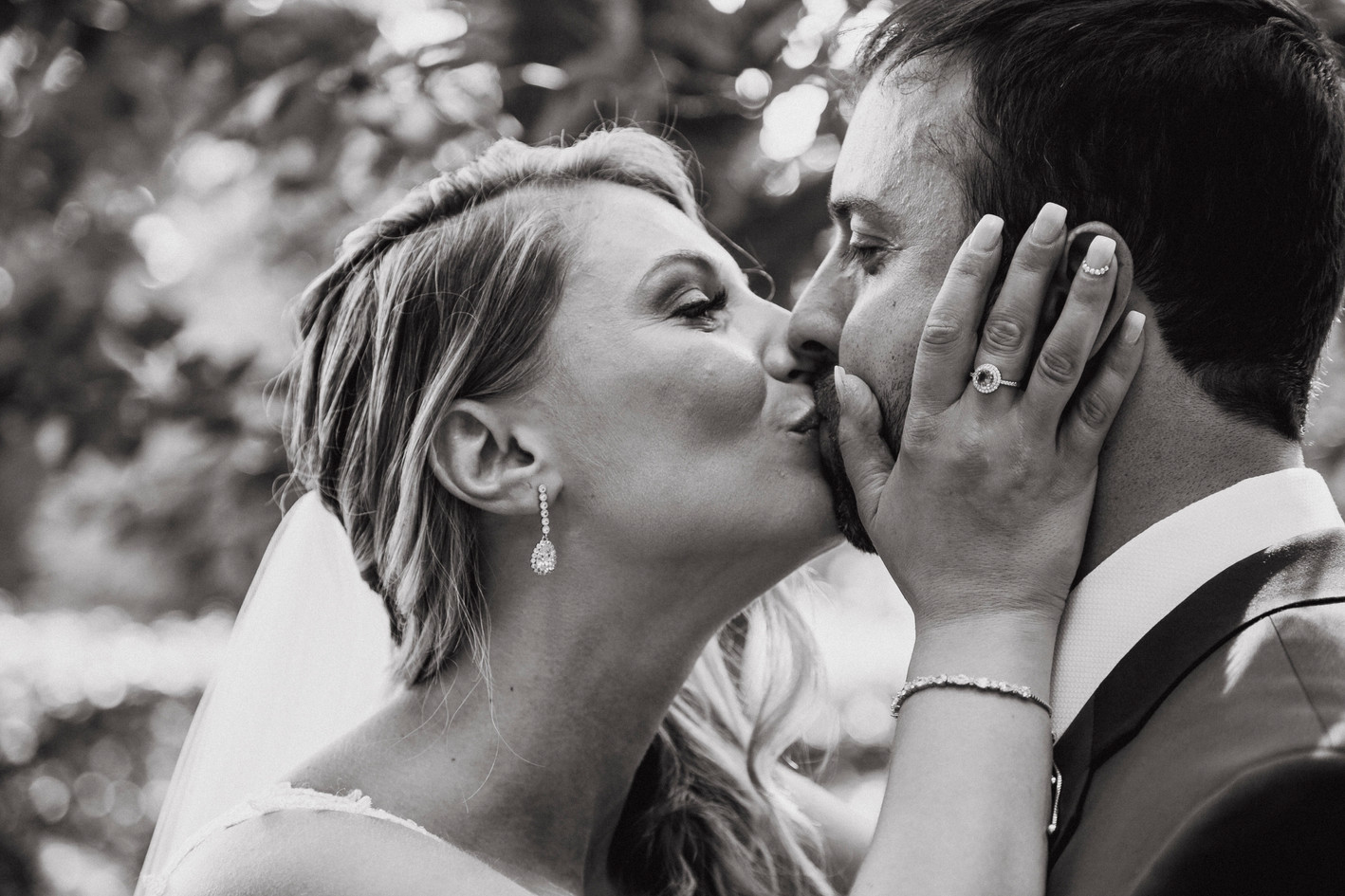 Bride holding Grooms face kissing his lips.