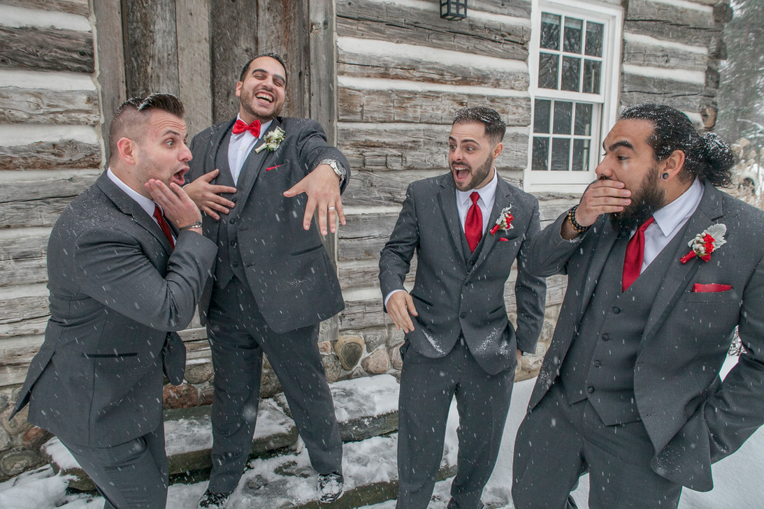 Groom and groomsmen looking at wedding band.