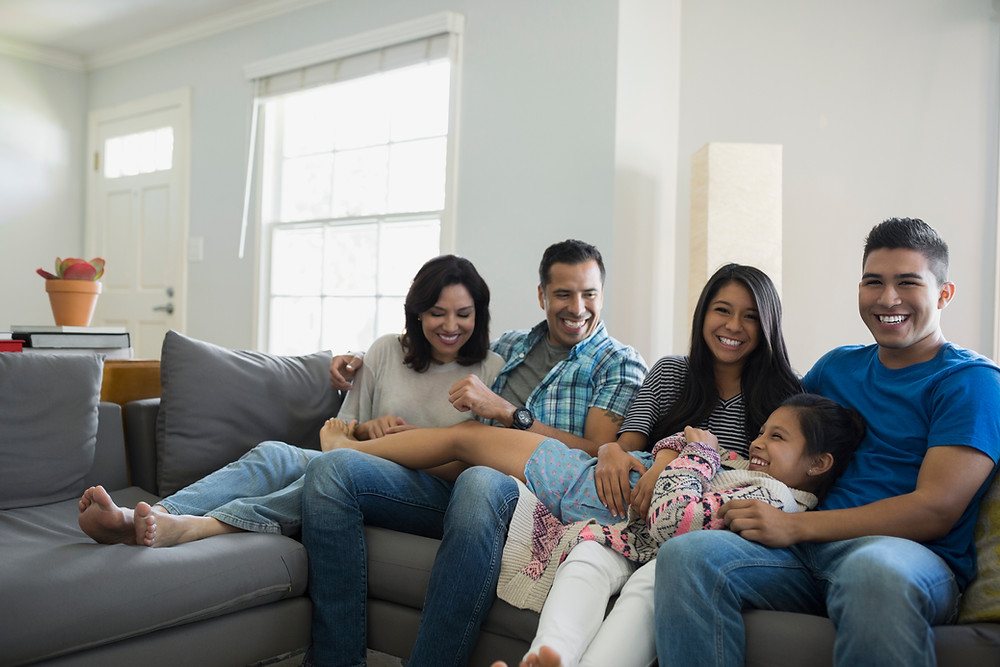 family smiling and sitting on couch at home