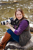 Picture of photographer with big camera and a river behind her