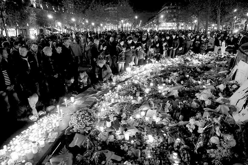 Dozens of mourning people captured during civil service in remembrance of November 2015 Paris attacks victims. Western Europe, France, Paris, place de la République, November 15, 2015.