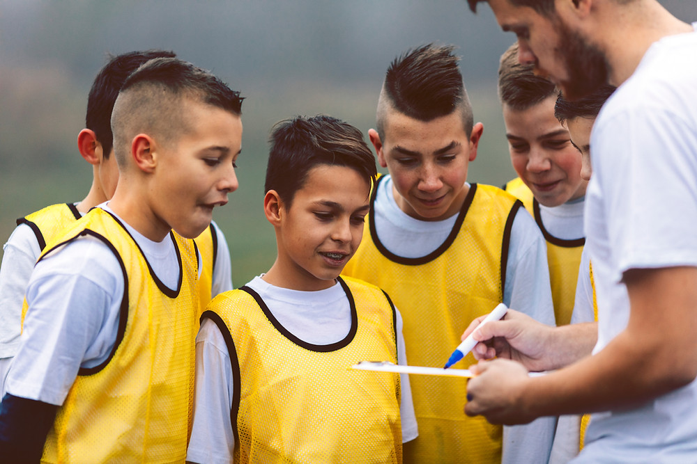 Coach discussing a play with a soccer team