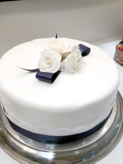 White fondant with lace and blue ribbon.