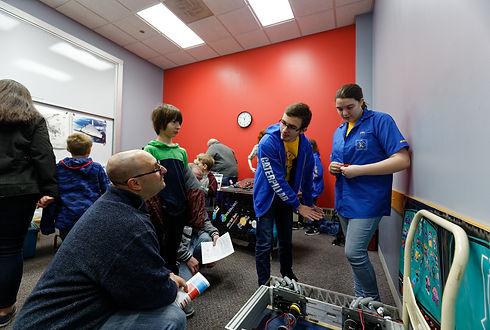 Roaring Robotics students showing off a robot drive train.
