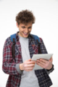 Happy male student standing with tablet