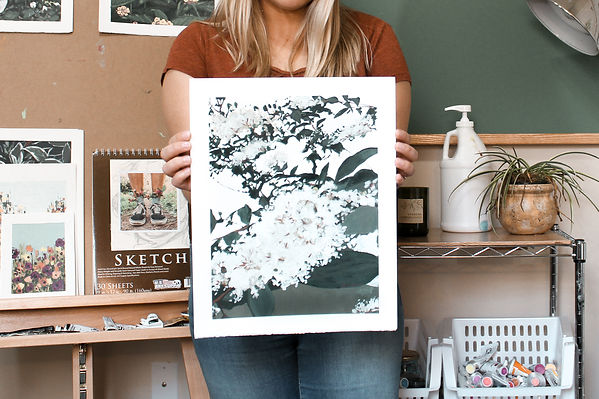 Artist Karli Corr is holding an original artwork in her art studio