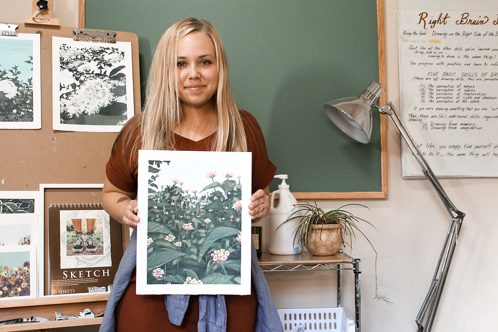 Karli Corr holding original floral art in her art studio