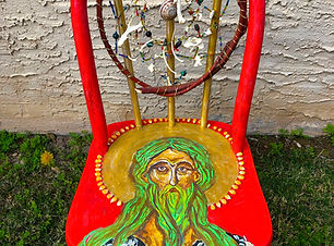 Red chair painted with saint with green beard and hair