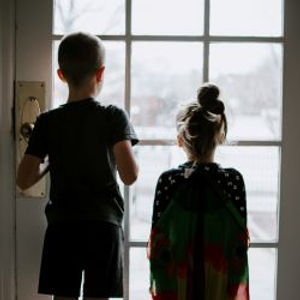 Two lonely children are looking outside