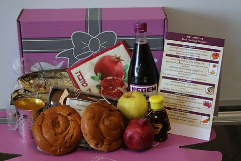 Purple box with Rosh Hashannah foods in front such as wine, bread, apples and honey