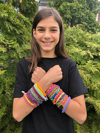 Image of Olivia with lots of colourful bracelets on both wrists