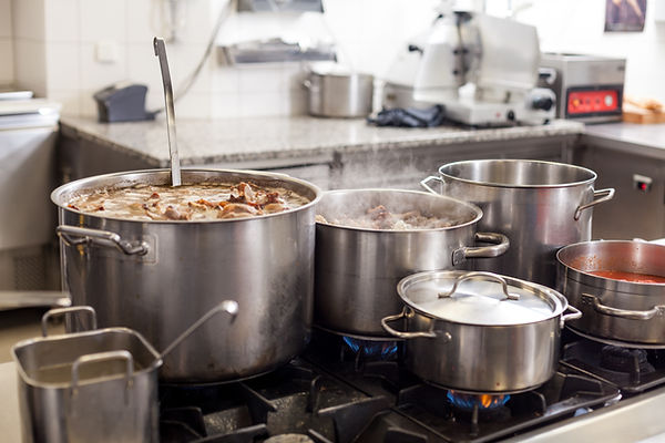 Commercial kitchen with large pots cooking soup.