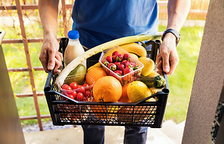 Person in a blue shirt holding a food hamper