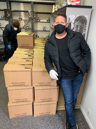 Volunteer at MAZON grantee standing in front of boxes wearing a mask