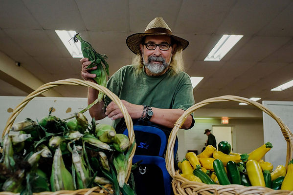 Male volunteer wearing a straw hat holding corn standing next to 2 baskets of corn and squash