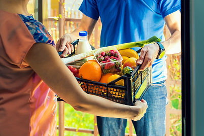 Person delivering a food hamper filled with fresh food