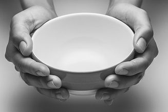 Black and white close up of hands holding an empty white bowl.