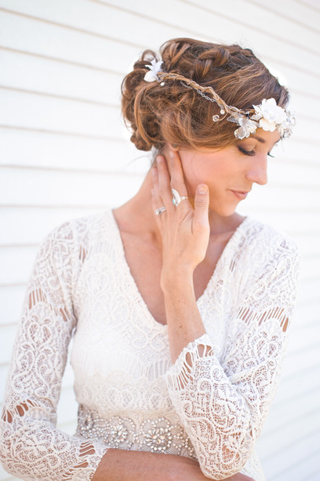 Bride in white lace dress in front of wh