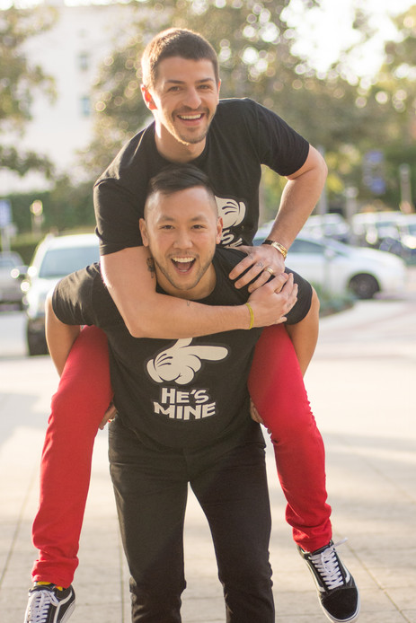 Male couple plays piggyback and laughs