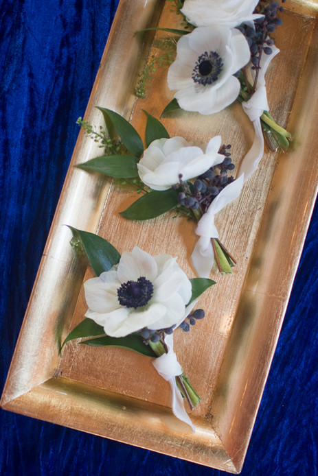 Three anemone boutonnieres on gold tray
