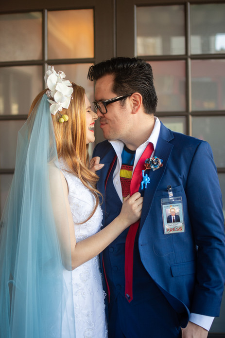Bride nuzzles groom in superman-themed s
