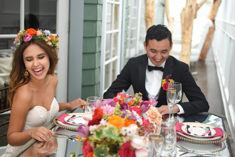 Bride and groom laugh at colorful table