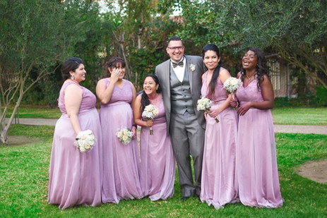 Man laughing with bridesmaids in purple