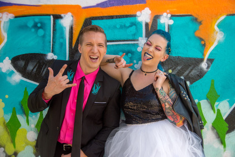 Punk bride and groom hold up rock hands