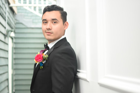 Groom leaning against white wall