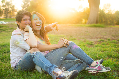 Couple covered in colored powders laughi