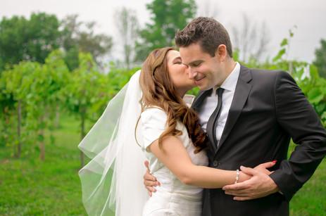 Bride kisses groom's cheek in vineyard