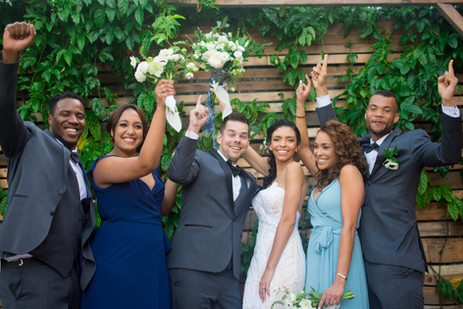 Wedding party celebrates with hands in t