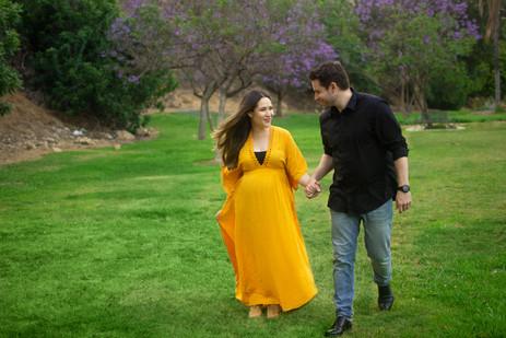 Pregnant woman in yellow dress walks han