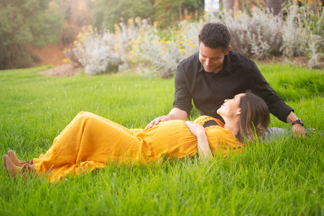 Pregnant woman in yellow dress lies on g