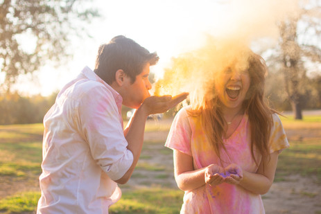 Playful couple playing with colored holi