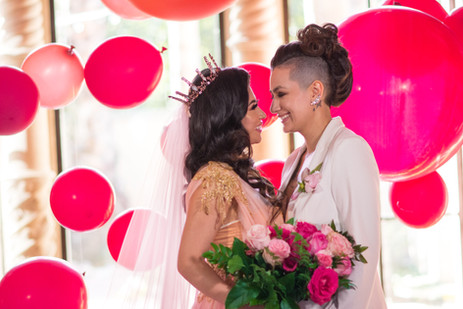 Lesbian brides surrounded by pink balloo