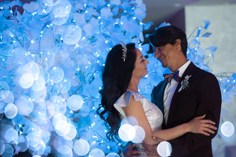 Married couple with lit blue tree and bo