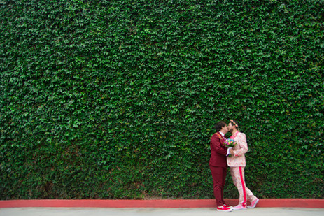 Fashionable grooms kiss in front of wall